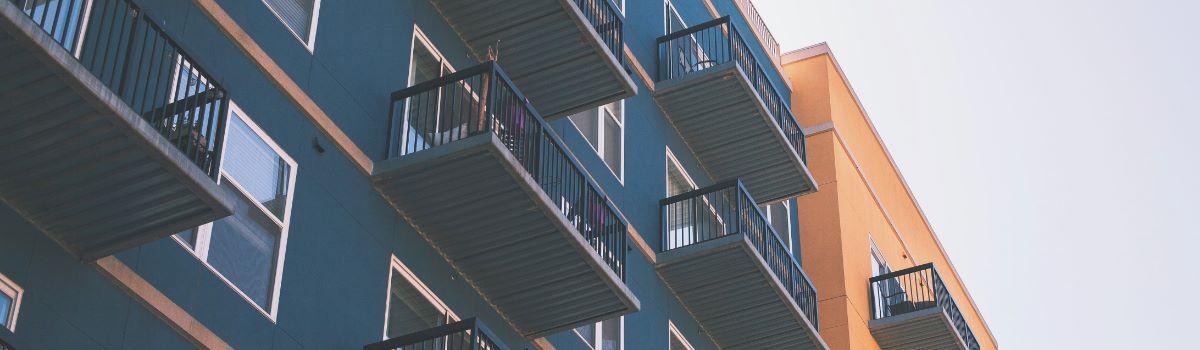 Blaue Fassade eines Mehrfamilienhauses mit Balkonen